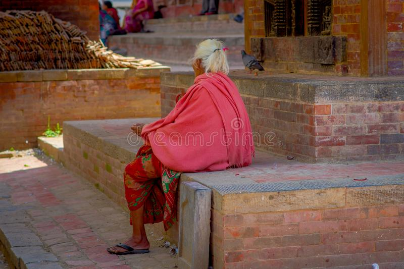 KATHMANDU, NEPAL OCTOBER 15, 2017: Unidentified nepalese old woman wearing a pink costume sitting at outdoors in a. Durbar square in a beautidul sunny day near royalty free stock photography