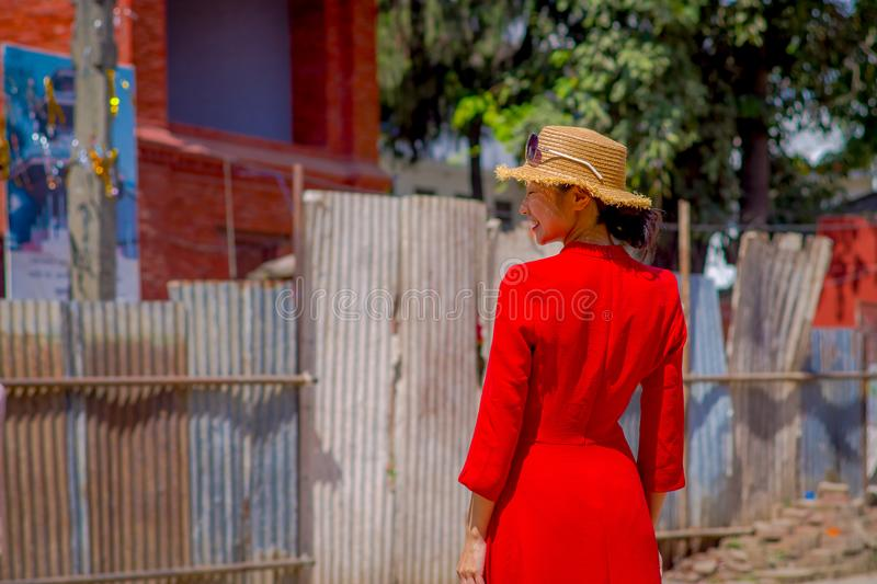 KATHMANDU, NEPAL OCTOBER 15, 2017: Unidentified nepalese woman wearing a red dress and a hat with sunglasses in her head. Posing for camera, in a Durbar square royalty free stock photo