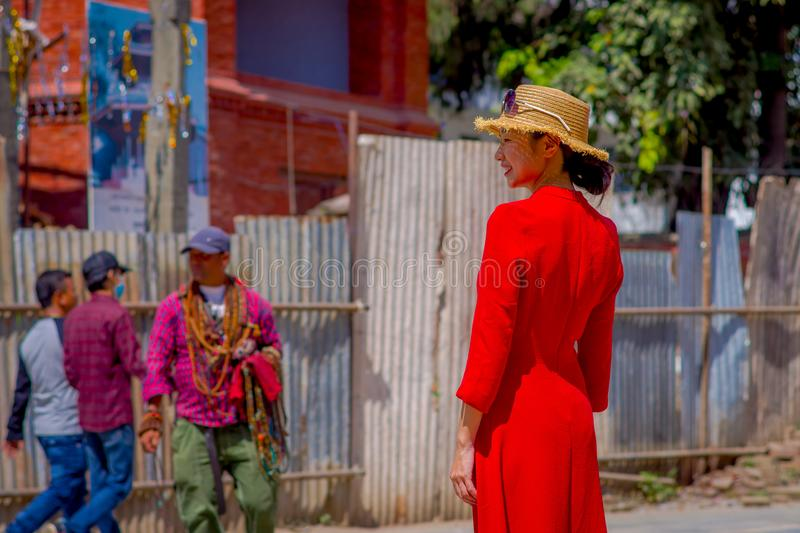 KATHMANDU, NEPAL OCTOBER 15, 2017: Unidentified nepalese woman wearing a red dress and a hat with sunglasses in her head. Posing for camera, in a Durbar square stock image