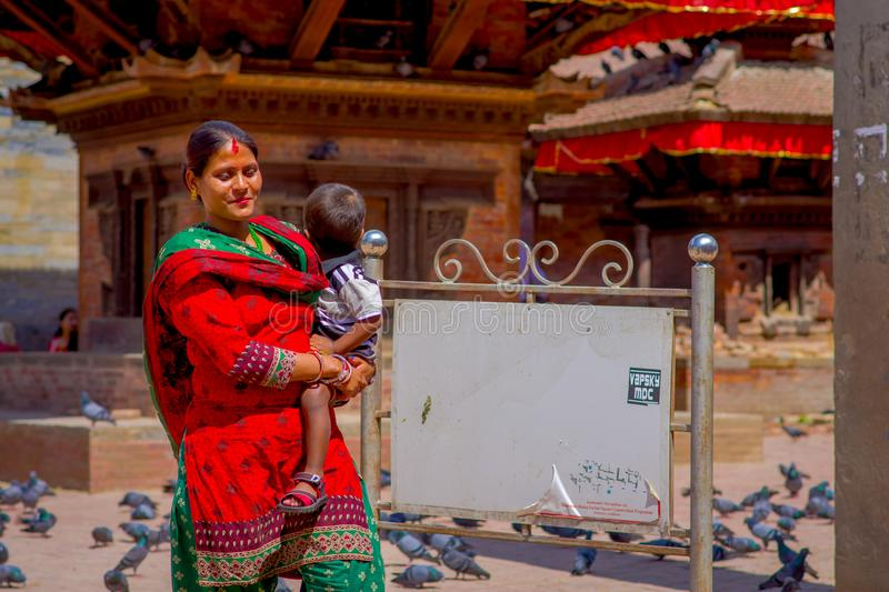 KATHMANDU, NEPAL OCTOBER 15, 2017: Unidentified nepalese woman wearing typical clothes and carrying a baby in her arms. Posing for camera, in a Durbar square stock photos