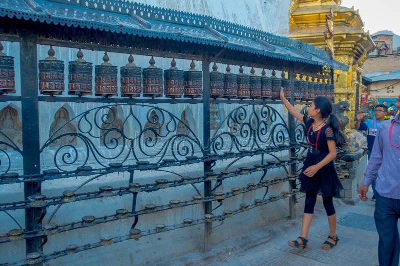 KATHMANDU, NEPAL OCTOBER 15, 2017: Unidentified people walking at outdoors close to Nepalese religious carvings and. Prayer wheels at Swayambhu Temple also royalty free stock images