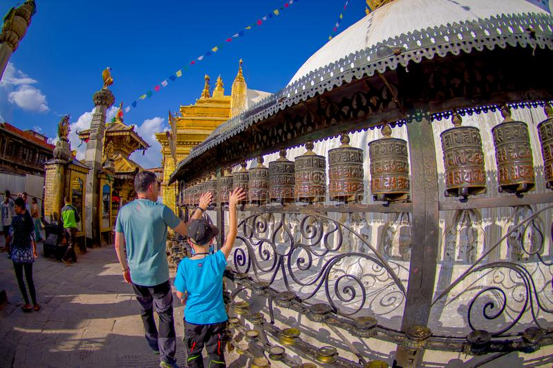 KATHMANDU, NEPAL OCTOBER 15, 2017: Unidentified people walking at outdoors close to Nepalese religious carvings and. Prayer wheels at Swayambhu Temple also royalty free stock photos