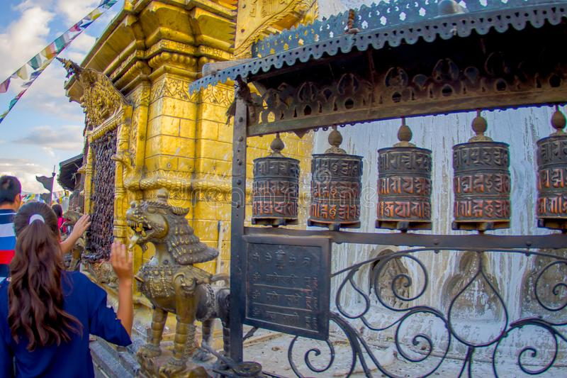 KATHMANDU, NEPAL OCTOBER 15, 2017: Unidentified people walking at outdoors close to Nepalese religious carvings and. Prayer wheels at Swayambhu Temple also stock photos