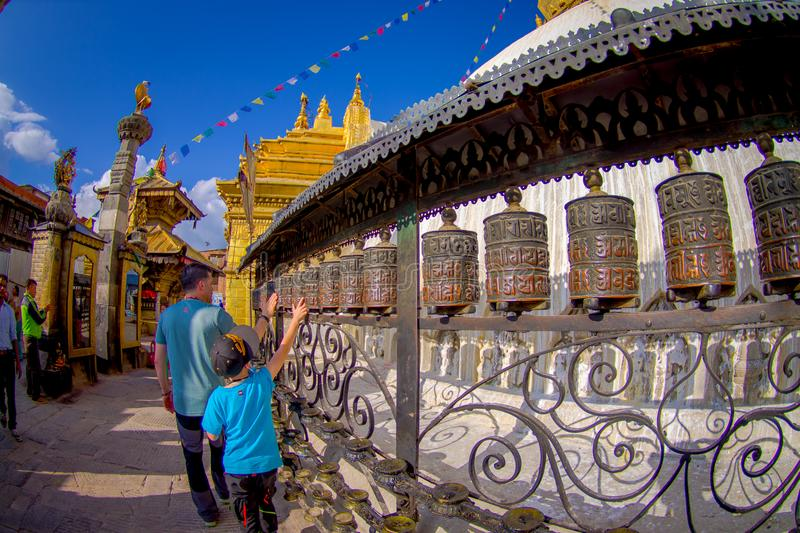 KATHMANDU, NEPAL OCTOBER 15, 2017: Unidentified people walking at outdoors close to Nepalese religious carvings and. Prayer wheels at Swayambhu Temple also royalty free stock image