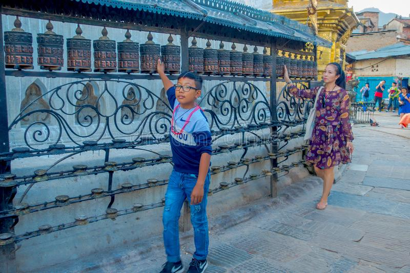 KATHMANDU, NEPAL OCTOBER 15, 2017: Unidentified people walking at outdoors close to Nepalese religious carvings and. Prayer wheels at Swayambhu Temple also stock image