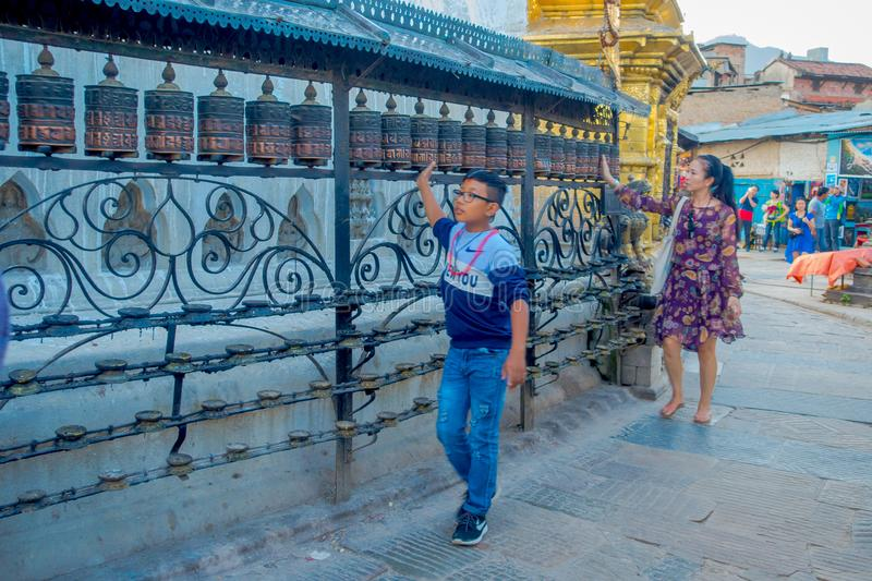KATHMANDU, NEPAL OCTOBER 15, 2017: Unidentified people walking at outdoors close to Nepalese religious carvings and. Prayer wheels at Swayambhu Temple also stock images