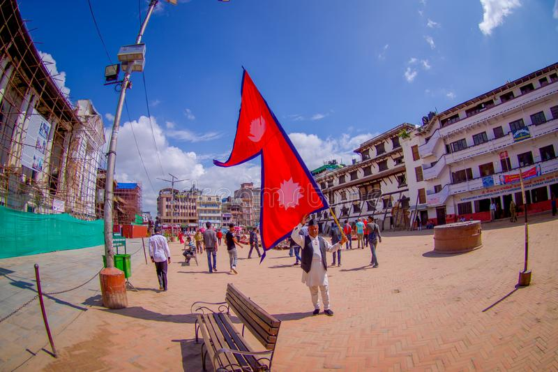 KATHMANDU, NEPAL OCTOBER 15, 2017: Unidentified people walking in the streets and a nepalese man holding a flag in his. Hands in Durbar square in Kathmandu royalty free stock photo