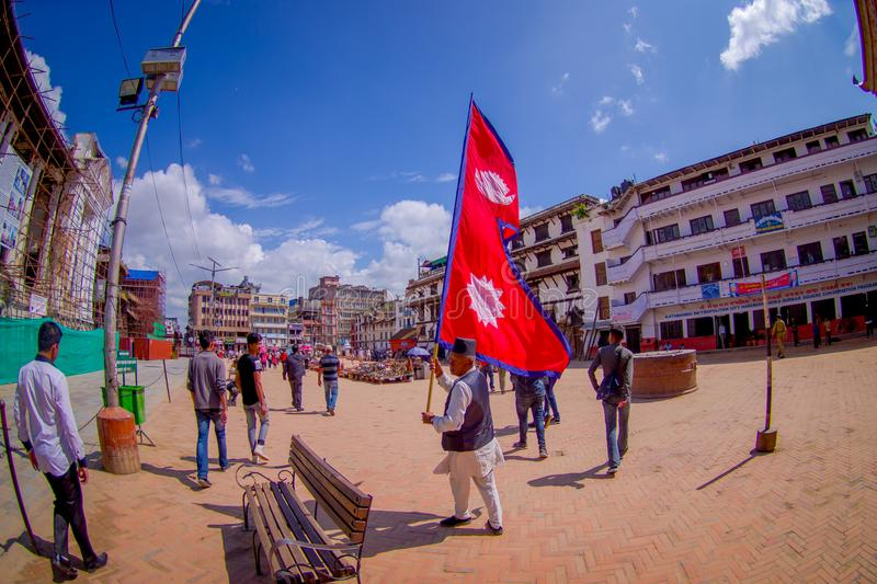 KATHMANDU, NEPAL OCTOBER 15, 2017: Unidentified people walking in the streets and a nepalese man holding a flag in his stock photo
