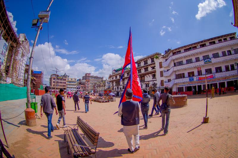 KATHMANDU, NEPAL OCTOBER 15, 2017: Unidentified people walking in the streets and a nepalese man holding a flag in his. Hands in Durbar square in Kathmandu stock photo