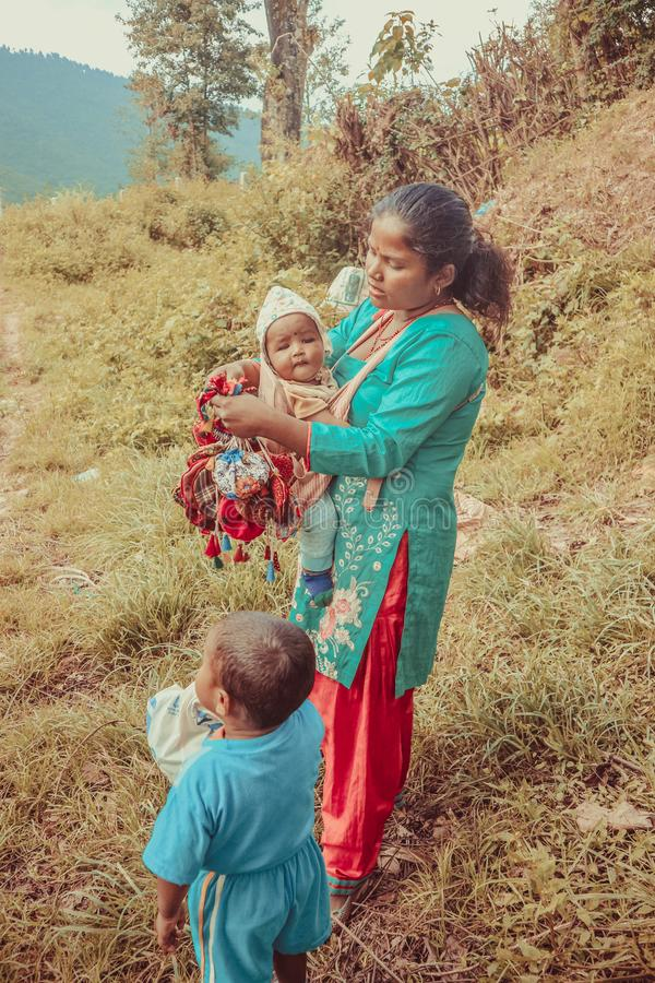 Kathmandu, Nepal - September 22, 2016: Nepalese mother carrying her baby and holding colorful bags in the village, Nepal stock photos