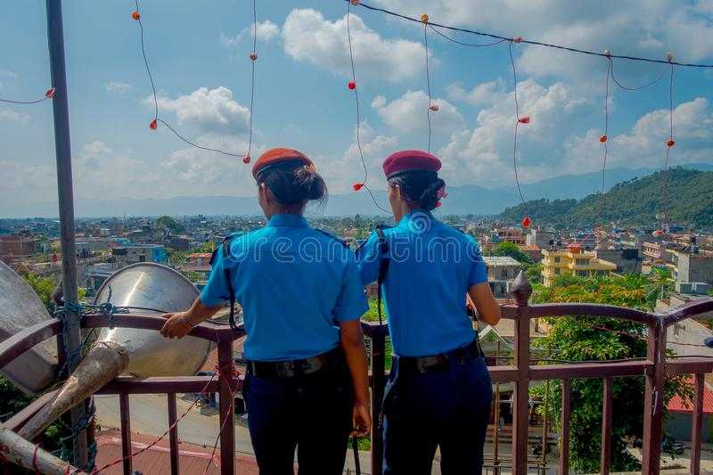 KATHMANDU, NEPAL - SEPTEMBER 04, 2017: Portrait of two women guards giving a back to the camera, from the Nepalese Army. Posing for camera at the enter of stock photography