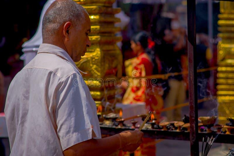 KATHMANDU, NEPAL - SEPTEMBER 04, 2017: Close up of unidentified Nepalese man burning incense in traditional clothes of. KATHMANDU, NEPAL - SEPTEMBER 04, 2017 stock image