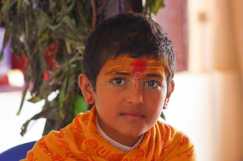 KATHMANDU, NEPAL - SEPTEMBER 04, 2017: Portrait of young Nepalese boy wearing typical clothes and some orange and red. Color in his forehead, in Nepal royalty free stock images