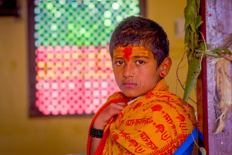 KATHMANDU, NEPAL - SEPTEMBER 04, 2017: Portrait of young Nepalese boy wearing typical clothes and some orange and red. Color in his forehead, in Nepal stock photo