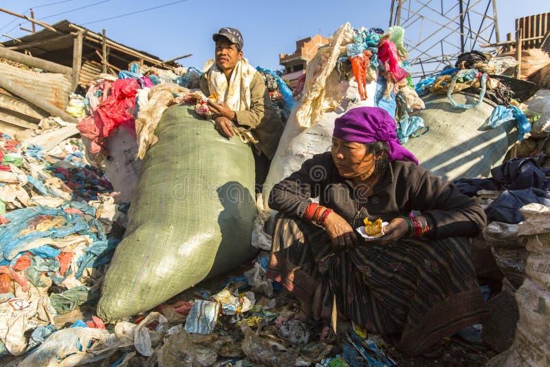 KATHMANDU, NEPAL - Unidentified local poor people during lunch in break between working on dump. stock photo