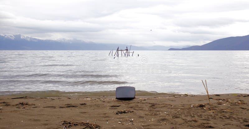Kathode Ray Tube auf Strand von See Prespa in Macedonia Ölbarrel und Weltkarte stockbilder