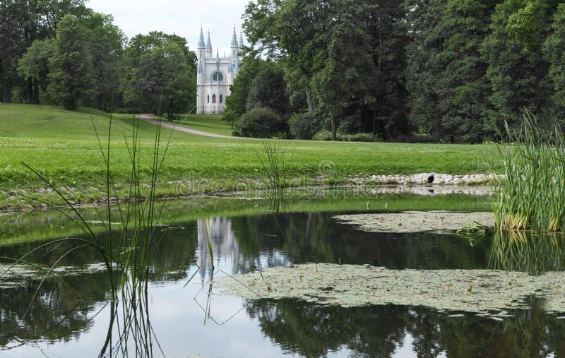 Katholieke kapel onder de bomen dichtbij de vijver met riet royalty-vrije stock fotografie