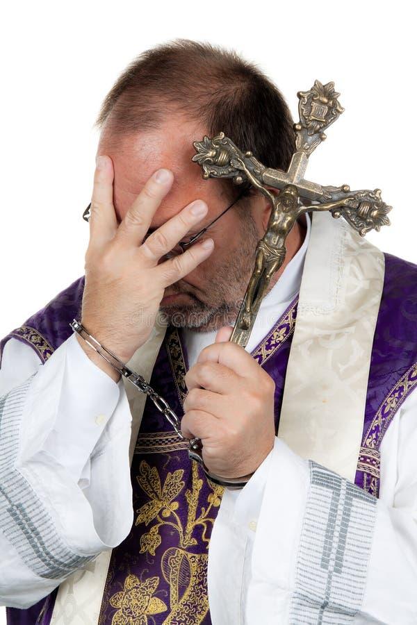 Katholischer Priester mit Handschellen. Missbrauch. stockfotografie