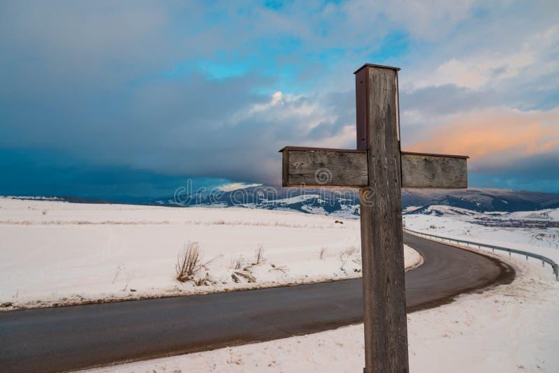Katholisches Kreuz der einfachen Eiche, gebogene Asphaltstraße, schneebedeckte Berge stockfotografie