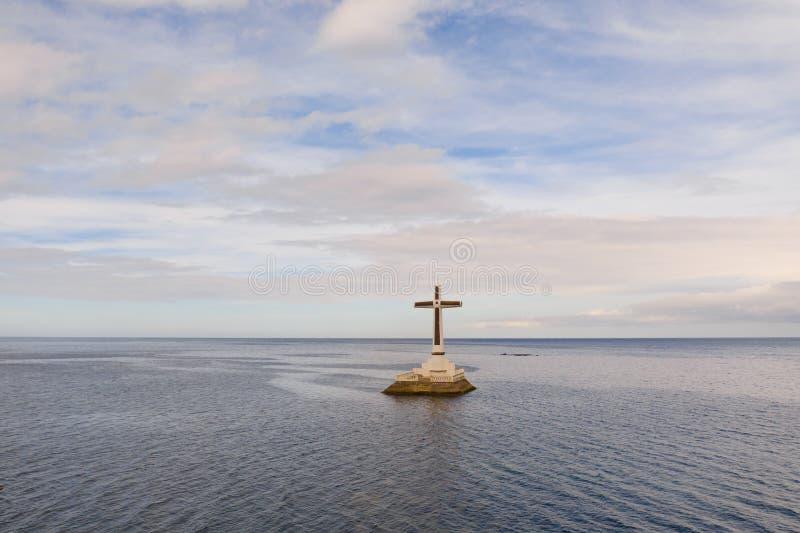 Katholisches Kreuz in einem überschwemmten Kirchhof im Meer nahe der Insel von Camiguin lizenzfreies stockbild