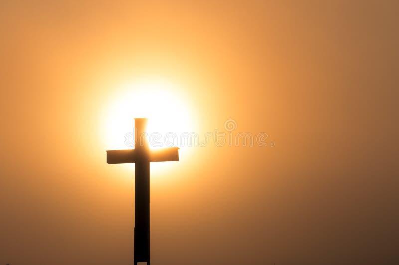 Katholisches Kreuz im Sonnenuntergang stockfotografie
