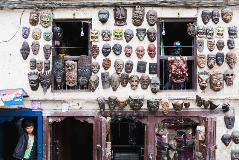 KATMANDOU, NÉPAL - AVRIL 2015 : position de garçon à côté de la façade de l'atelier de masque photo stock