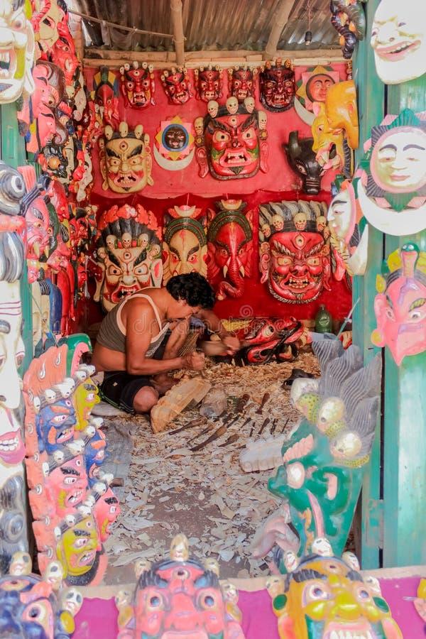 Katmandou, Népal - 4 novembre 2016 : Vue de face d'un artisan découpant le masque tibétain dans un art de boutique de souvenirs à image libre de droits