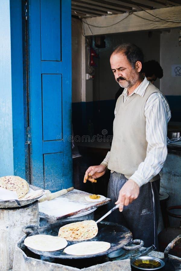 KATMANDU, NEPAL - APRIL 2015: kok die rotibrood in zijn open straatwinkel maken stock foto