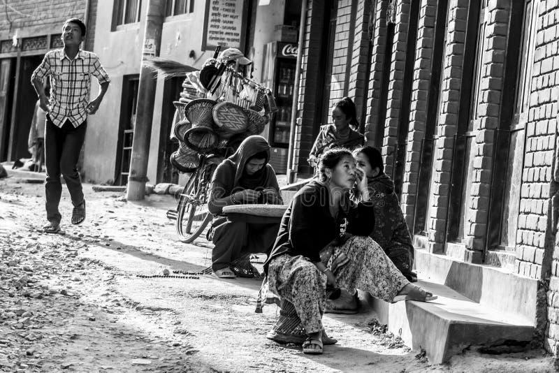 Katmandu, Nepal - 5 de noviembre de 2015: Gente nepalesa que se sienta a lo largo de una calle en Katmandu central foto de archivo