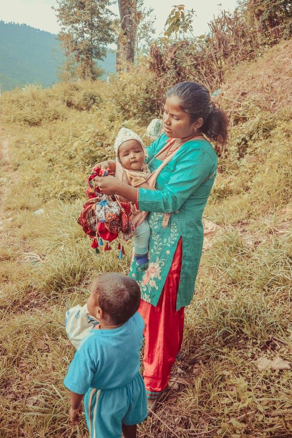 Katmandu, Nepal - 22 de septiembre de 2016: Madre nepalesa que lleva a su bebé y que celebra bolsos coloridos en el pueblo, Nepal fotos de archivo
