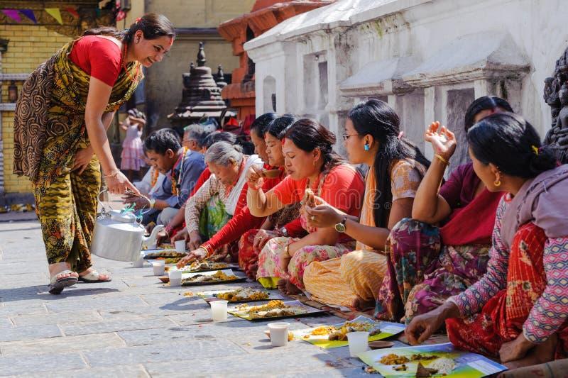 KATMANDU NEPAL - JULI 09, 2011: Folk som har mat på den öppna bröllopslunchen i Swayambhunath tempelträdgård Swoyambhunath är royaltyfria foton