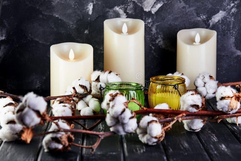 Katoenen bloemen die op een donkere houten achtergrond en kaarsen liggen stock foto's