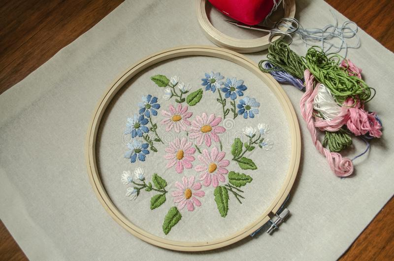 Katoenen stof met geborduurd die boeket van wildflowers met houten hoepels, gekleurde draden, schaar en een rood hoofdkussen voor royalty-vrije stock afbeeldingen