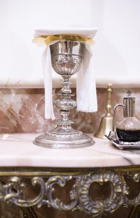 Katolicki liturgiczny chalice, wino miotacz i dzwon, zdjęcia stock