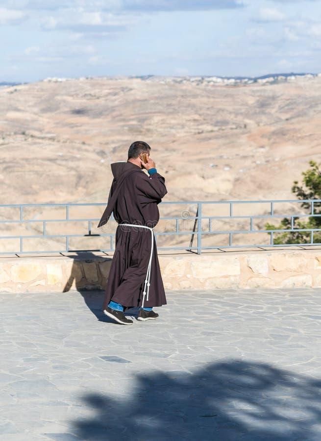 Katolicki michaelita mówi na jego telefonie komórkowym i chodzi na tarasie w podwórzu Pamiątkowy kościół Mojżesz na górze Nebo bl obrazy royalty free