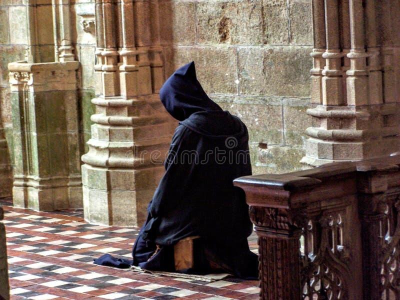 Katolik Christian Monk som knäfaller i den ödmjuka bönen som frågar gud för hjälp arkivfoto