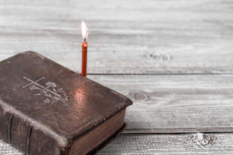 Katolsk bibel och röd kyrklig brinnande stearinljus på träbakgrund med kopieringsutrymme arkivbild