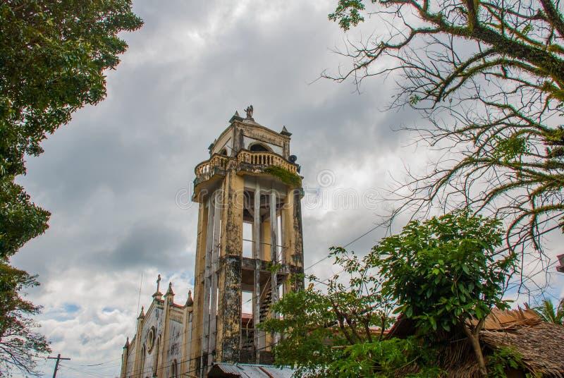 Katolsk domkyrka på bakgrunden av trädfilialer i Filippinerna Pandan Panay royaltyfria bilder