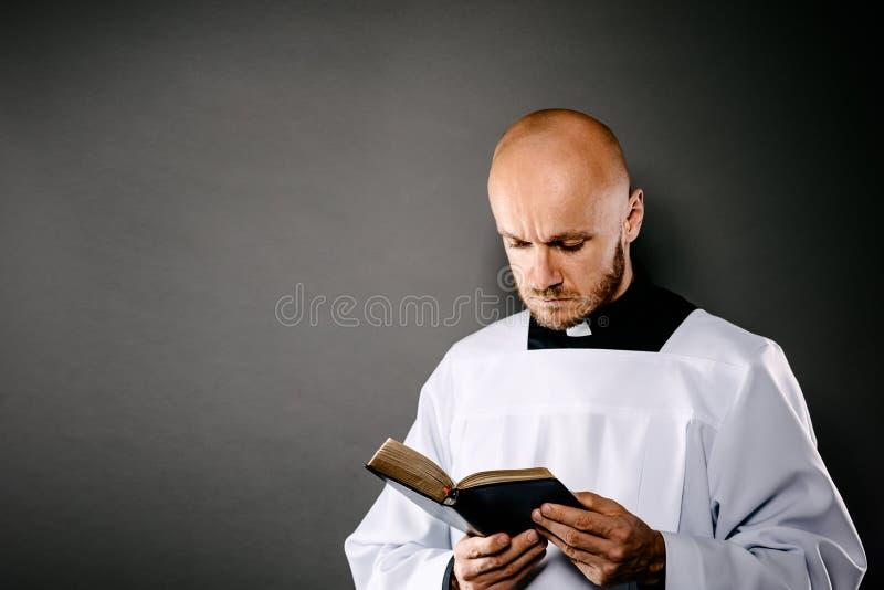 Katolsk präst i den vita mässkjortaläsningbibeln arkivbilder
