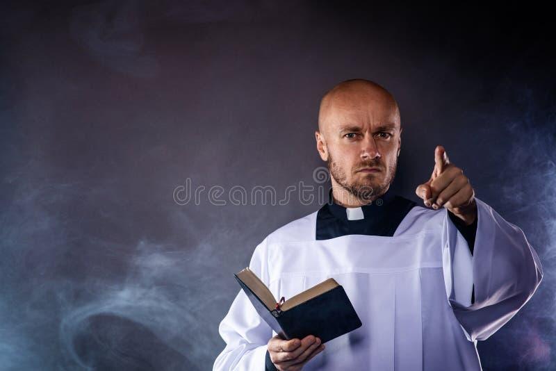 Katolsk präst i den vita mässkjortan och svart skjorta med bibeln för prästmankrageläsning royaltyfri bild
