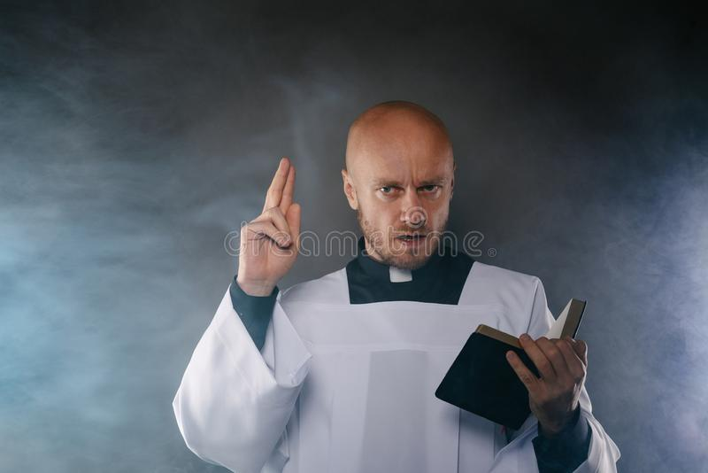 Katolsk präst i den vita mässkjortan och svart skjorta med bibeln för prästmankrageläsning arkivfoto