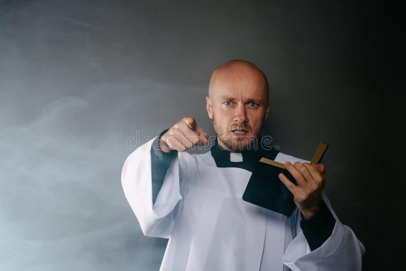 Katolsk präst i den vita mässkjortan och svart skjorta med bibeln för prästmankrageläsning arkivfoton