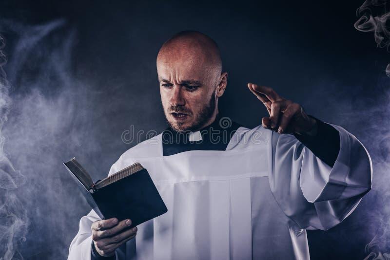 Katolsk präst i den vita mässkjortan och svart skjorta med bibeln för prästmankrageläsning arkivbilder