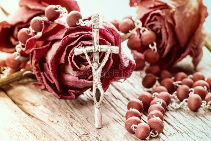 Katolsk radband och torra rosor arkivbild