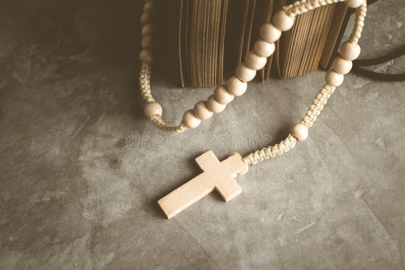 Katolska radbandpärlor med den gamla boken på cement bordlägger bönen, rosa royaltyfria bilder