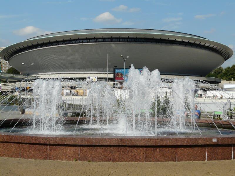 KATOWICE, SILESIA, Polonia-fuente en el cruce giratorio y el pasillo de deportes centrales Spodek fotos de archivo libres de regalías