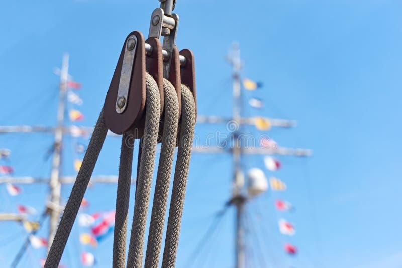 Katrol met kabels tegen een blauwe hemel en masten met gekleurde vlaggen stock afbeeldingen