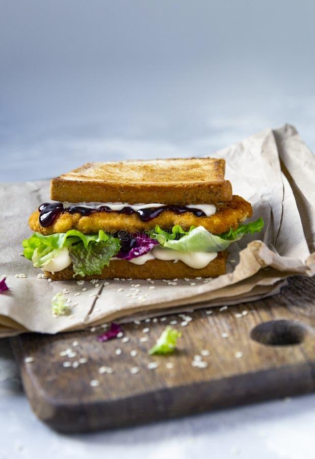 Katsu Sando allo scrittorio di legno - panino giapponese di tendenza dell'alimento con la cotoletta del pollo, il cavolo e la sal fotografia stock