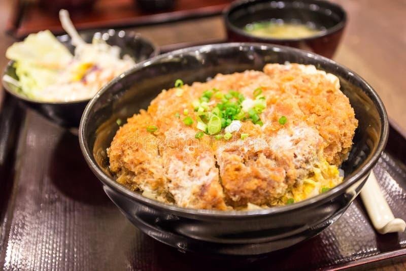 Katsudon - cotoletta fritta nel grasso bollente della carne di maiale impanata giapponese (tonkatsu) a fotografia stock