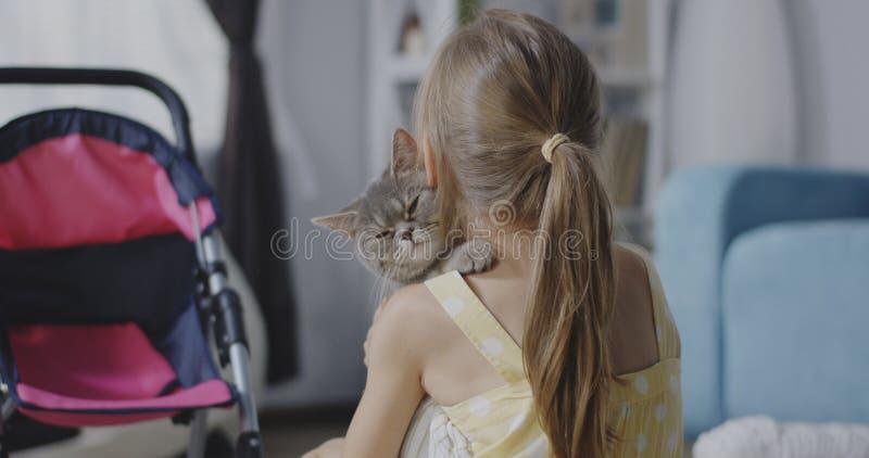 Katten som ligger på flickor, knuffar royaltyfria bilder